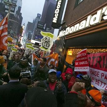 Demonstrators rally for better wages outside a McDonald's restaurant in New York (AP)
