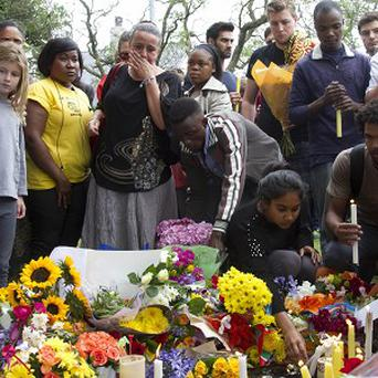 Mourners lay floral and candle tributes to Nelson Mandela outside his Johannesburg home (AP)