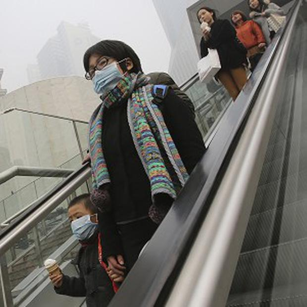 A woman and a child wear masks to protect them from air pollution in Shanghai, China (AP)