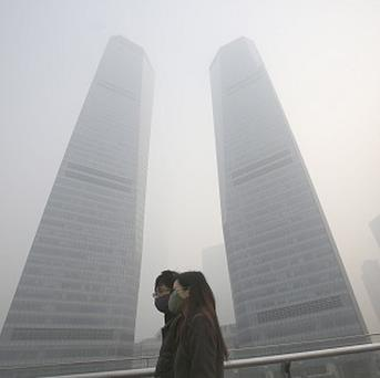 A couple in protective masks walk under the haze in Shanghai, China (AP)