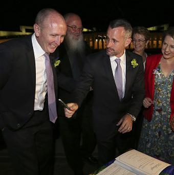 Stephen Dawson and his partner Dennis Liddelow sign the wedding register in front of Parliament House in Canberra, Australia (AP)