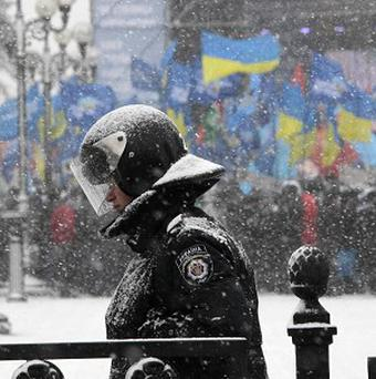 A police officer guards the Ukrainian Parliament as supporters of president Viktor Yanukovych stand in the background in Kiev (AP)