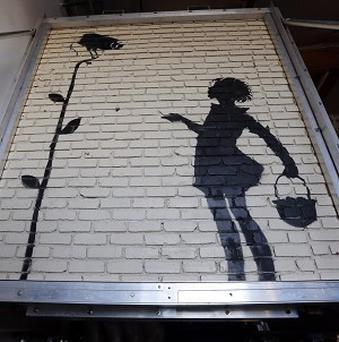 Banksy's Flower Girl stencil has fetched £128,200 at a Beverly Hills auction. (AP /Reed Saxon)