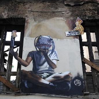 Graffiti on a burned house in Athens where a 15-year old boy was killed by police in 2008. (AP/Dimitri Messinis)