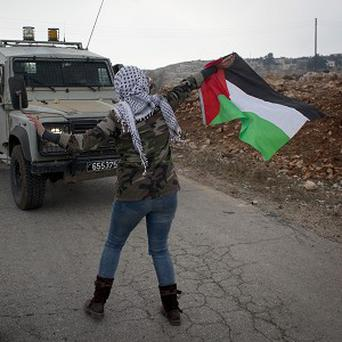 Palestinian protesters block the road in front of an Israeli police vehicle (AP)