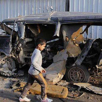 An Iraqi boy walks past a damaged vehicle after a car bomb attack in the Sadr City neighbourhood of Baghdad (AP)
