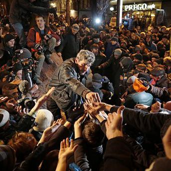 A protester hands out pieces of Lenin's toppled statue in Kiev, Ukraine. (AP)