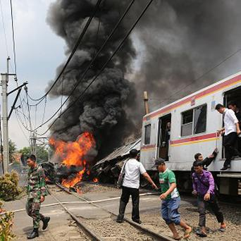 People escape after a commuter train collided with a truck hauling fuel on the outskirts of Jakarta, Indonesia (AP)