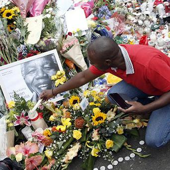 A mourner places a candle outside the home of former president Nelson Mandela in Johannesburg, South Africa (AP)
