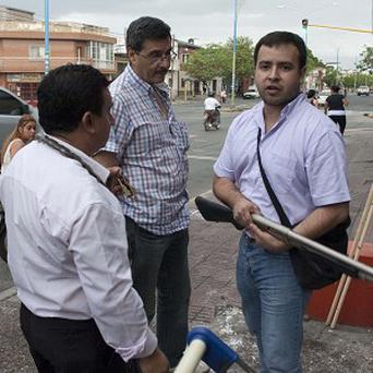 An armed shopkeeper outside his business after his shop was looted in San Miguel de Tucuman, Argentina