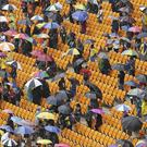 People shelter from the rain during the memorial service for former South African president Nelson Mandela at the FNB Stadium in Soweto (AP)
