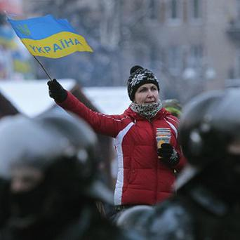 A pro-European Union activist waves a Ukrainian national flag in front of a police line near a tent camp on Independence Square in Kiev, Ukraine (AP)