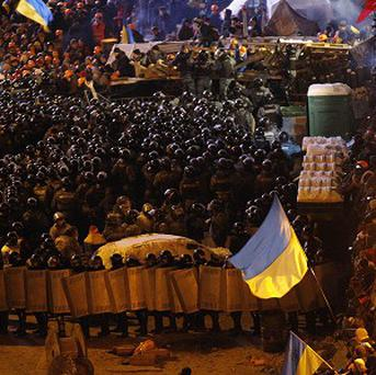 Ukrainian riot police face pro-European Union activists gather in their tent camps on the Independence Square in Kiev (AP)