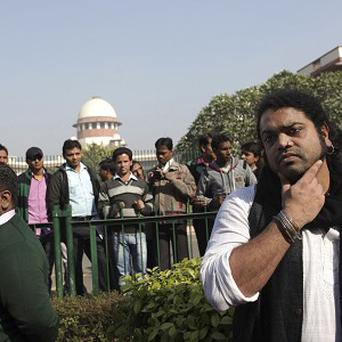 Indian gay rights activists and others stand outside the Supreme Court in New Delhi. (AP Photo/Tsering Topgyal)