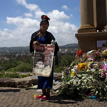 A woman poses for a snapshot with a picture of Nelson Mandela at the Union Buildings in Pretoria where his body lies in state (AP)