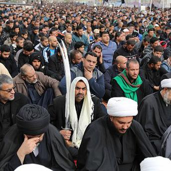Followers of Shiite cleric Muqtada al-Sadr crowd a street as they attend open air Friday prayers in Baghdad (AP)