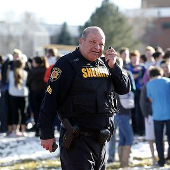 A sheriff deputy talks on his radio at Arapahoe High School in Centennial, Colorado (AP)