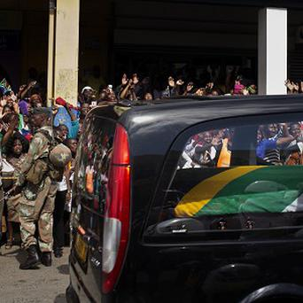 The motorcade transporting the body of Nelson Mandela, in black hearse, passes through crowds of mourners gathered in the town of on its way to Qunu, South Africa (AP)
