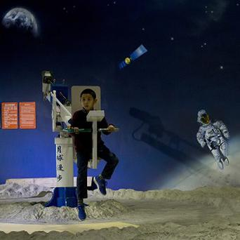 A child tries out a moonwalker device at the China Science and Technology Museum in Beijing (AP)