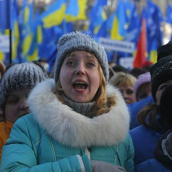 Supporters of Mr Yanukovych's party greet prime minister Mykola Azarov after his speech during their rally in Kiev (AP)