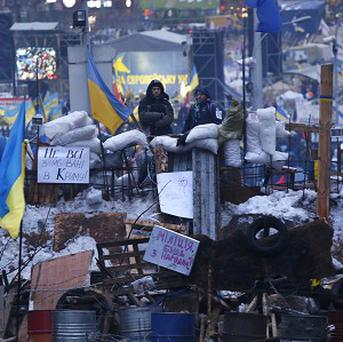 Pro-European Union activists stand on top of barricades during a rally in Independence Square in Kiev, Ukraine (AP)