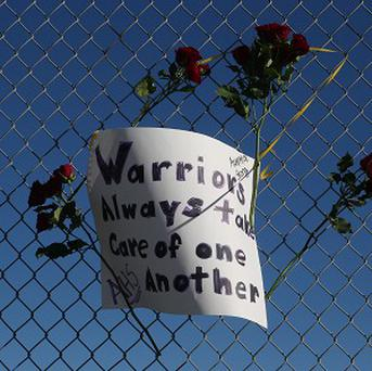 Roses and a sign of support are woven into a cyclone fence around a tennis court at Arapahoe High School in Centennial, Colorado (AP)