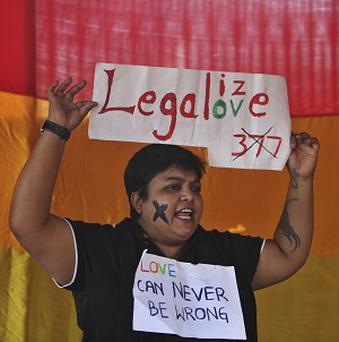An Indian gay rights activist holds a placard during the protest against the criminalisation of homosexuality (AP)