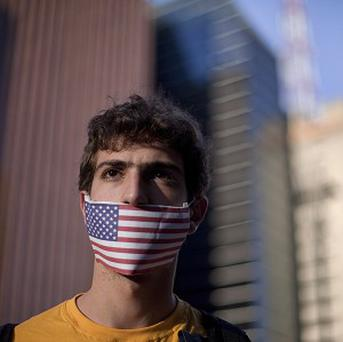 A protester wearing a US flag over his mouth demonstrates in Sao Paulo, Brazil (AP)