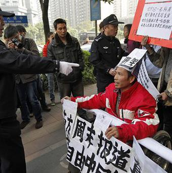 A Chinese policeman prepares to arrest a wheelchair protester - lawyers say the country is hoping to hide a crackdown over Christmas (AP)