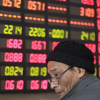 An investor looks at the stock price monitor at a private securities company in Shanghai (AP)