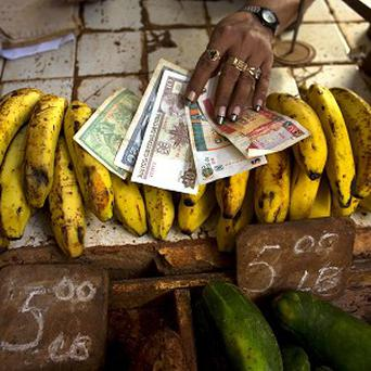 Two soon to be scrapped convertible pesos, right, alongside regular Cuban pesos at a food stall in Havana. (AP)