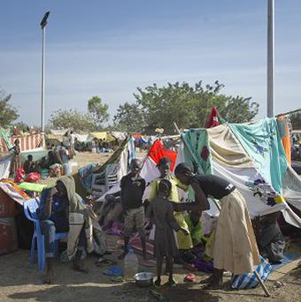A displaced family sits with their belongings after seeking refuge at the compound of the United Nations Mission in South Sudan. South Sudan, the world's newest country, is threatened by rapidly escalating ethnic violence.