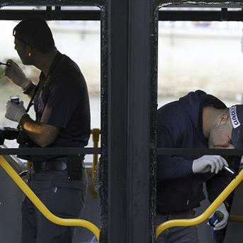 Police inspect a bus after a bomb planted on the vehicle exploded in a Tel Aviv suburb. (AP)