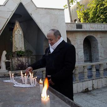 An Iraqi Christian lights candles at the Chaldean Church of Virgin Mary in Baghdad. Tens of thousands of Iraqi Christians fled Iraq since the US-led invasion in 2003 (AP)