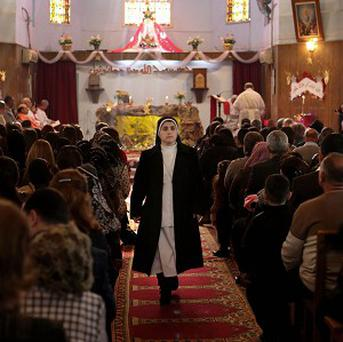 A nun walks as worshippers attend a Christmas mass at the Mother Teresa Catholic Church in Basra, Iraq's second-largest city (AP)