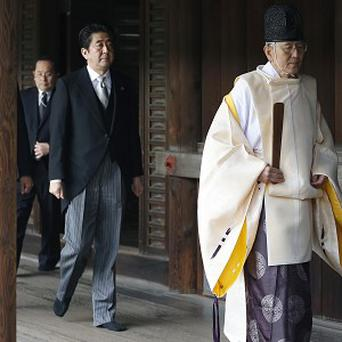 Japanese Prime Minister Shinzo Abe, second from right, follows a Shinto priest to pay respect for the war dead at Yasukuni Shrine in Tokyo.