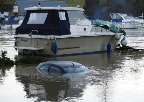 A boat floats next to a submerged car at a marina following heavy rain in East Farleigh, southern England