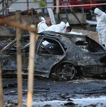 Lebanese army investigators in white overalls inspect the scene of an explosion in central Beirut which killed several people including Mohammed Chatah, a senior aide to former Lebanese prime minister Saad Hariri (AP)
