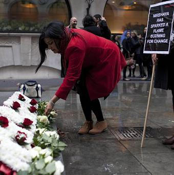 Campaign supporters in London place white roses at a wreath during a memorial event to remember Jyoti Singh, the 23-year-old victim of a fatal gang rape on a Delhi bus.