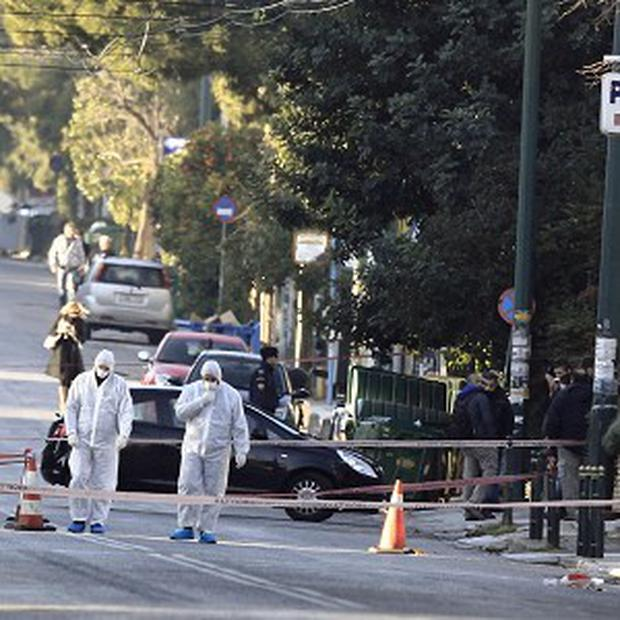Police investigate a street outside the residence of German ambassador Wolfgang Dold in the northern suburb of Halandri (AP)