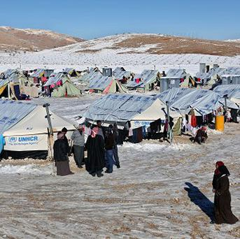 Syrian refugees walk outside their tents at a refugee camp in the eastern Lebanese border town of Arsal (AP)
