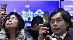 Visitors take photos of stock prices on monitors at the end of a ceremony to wrap up the year's trading on the Tokyo Stock Exchange (AP)