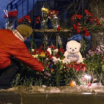 A women places a flower outside a wreckage of a trolleybus in Volgograd after a suicide bombing killed 14 people (AP)
