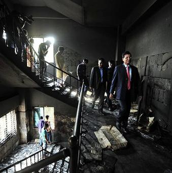 Bangladeshi officials inspect the burned out garment factory on the outskirts of Dhaka (AP)