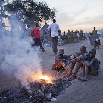 Displaced boys who fled the recent fighting between government and rebel forces sit around a fire in South Sudan. (AP)