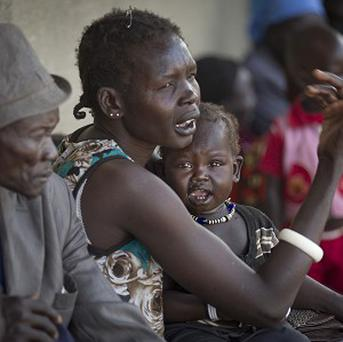 Displaced people who fled from recent fighting in Bor queue outside a clinic run by Medecins Sans Frontieres in the town of Awerial, South Sudan (AP)