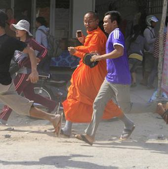A Cambodian Buddhist monk and garment workers run to safety in front of a factory on the outskirts of Phnom Penh (AP)