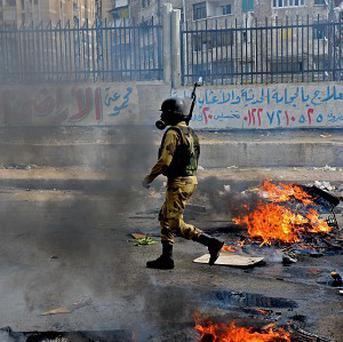 A soldier walks through heavy smoke from clashes with Muslim Brotherhood supporters in Alexandria (AP)