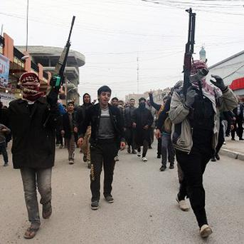 Mourners and Sunni gunmen chant slogans against Iraq's Shiite-led government during the funeral of a man killed when clashes erupted between al Qaida gunmen and Iraqi army soldiers in Fallujah (AP)