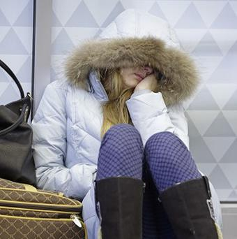 Anna Maksimkina, of Yekaterinburg, Russia, sleeps on the floor at Kennedy International Airport after a Delta flight from Toronto to New York skidded off the runway into a snow bank, temporarily halting all flights (AP)